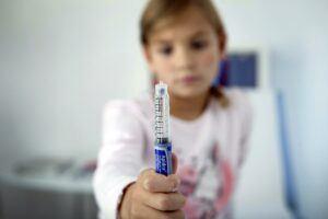 kid holding syringe