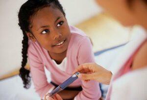 kid being monitored blood sugar level